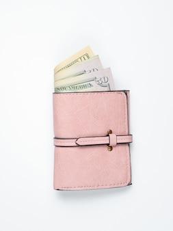 Модный кожаный кошелек с долларовых купюр на белой поверхности.