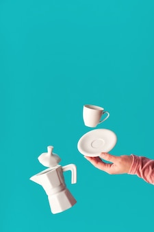 Trendy levitation flying coffee beans, espresso cup with saucer balancing on index finger of female hand. ceramic coffee maker levitation. trendy mint blue coffee wall, space for your text.
