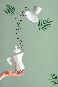 Trendy levitation. flying coffee beans and espresso cup with saucer. green mint wall with palm leaves, text space. ceramic stove coffee maker balancing on index finger of female hand.