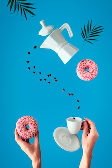 Trendy levitation. flying line of coffee beans between ceramic coffee maker and espresso cup with saucer. female hands hold pink doughnuts with sugar sprinkles. blue mint wall with palm leaves.