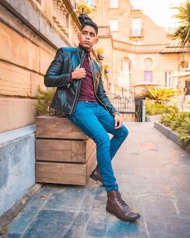 Модный образ жизни латиноамериканского парня в городе. джинсы, кожаная куртка и коричневые туфли