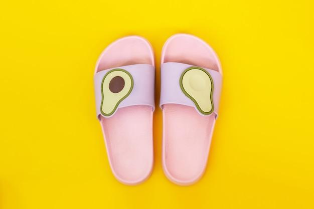 Модные светло-розовые и фиолетовые женские пляжные резиновые шлепанцы с половинками авокадо, изолированными на ярко-желтой стене