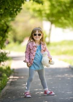 Trendy little girl in park with teddybear in hand