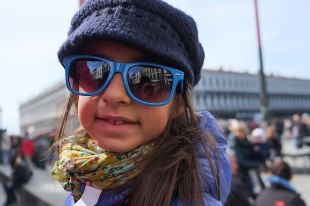 休暇中に笑顔のメガネを持つトレンディな少女..ヴェネツィアの幸せそうな顔。サングラス。