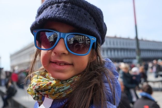 Trendy little girl with glasses smiling in vacation.. happy face in venice. sun glasses.