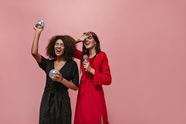 Ragazza alla moda dai capelli lunghi in abito rosso moderno che tiene il microfono e posa con una signora riccia in abiti neri con palle da discoteca in mano