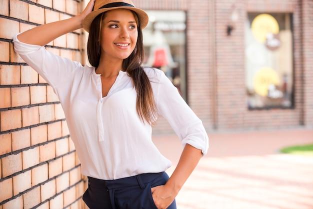 트렌디한 모습. 야외에서 벽에 기대어 팔짱을 끼고 웃고 있는 모자를 쓴 아름다운 젊은 여성