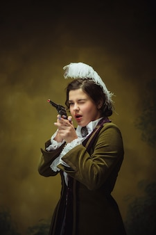 拳銃でルネッサンス時代のトレンディな外観の女性の肖像画
