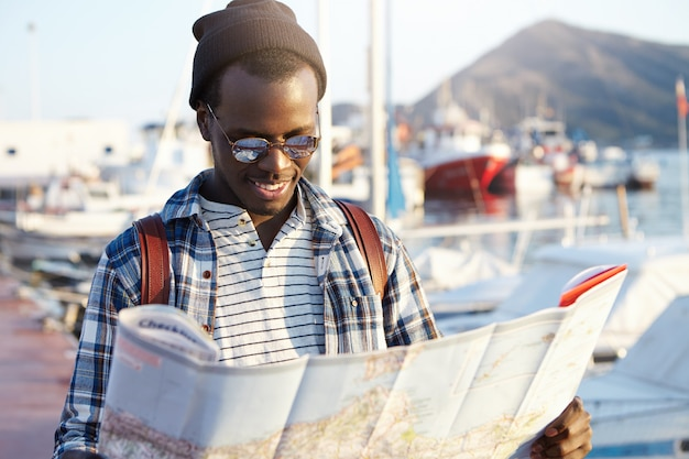 Trendy looking african american tourist with backpack in hat and sunglasses studying directions using city guide while exploring sights and landmarks of resort town