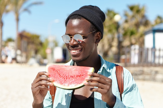 スタイリッシュなミラーレンズシェードと黒い帽子を身に着けているトレンディな陽気な若いアフリカ系アメリカ人男性学生都市ビーチで外の友達と夏の日を過ごしながら熟したスイカを食べる
