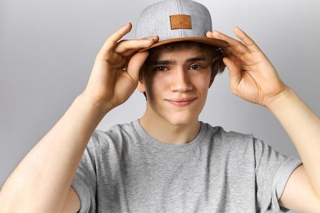 頭に野球帽を調整し、ピークに手をつないで自信を持って笑顔で見ているトレンディな見た目のクールな10代の少年。スナップバックを着ているかわいい男の子