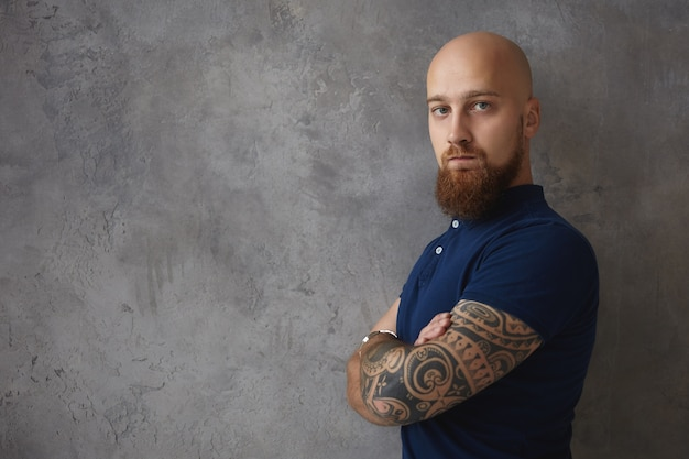 Модно выглядящий мачо с мускулистыми татуированными руками и подстриженной густой бородой позирует в помещении со скрещенными руками, недоволен или разочарован, преследует губы, демонстрирует отрицательное отношение