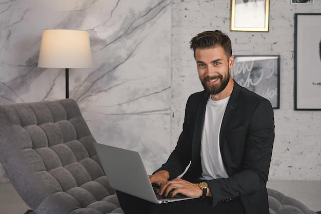 Trendy looking positive young unshaven male employee dressed in stylish luxurious clothes using generic laptop computer on sofa in modern office, rejoicing at success, smiling broadly