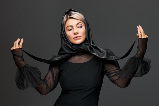 투명 블라우스를 입고 검은 가죽 머리 스카프를 목에 묶는 포즈를 취하는 예술적 매력적인 메이크업으로 트렌디 한 찾고 세련된 젊은 여성. 아름다움과 패션 컨셉