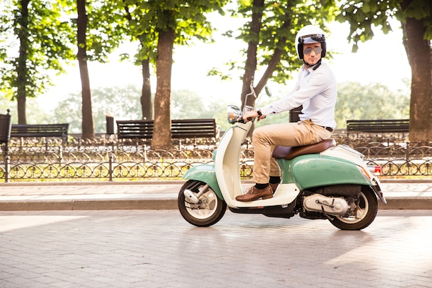 Trendy man driving a scooter in helmet