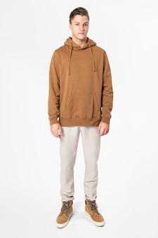 Модный мужчина в коричневой толстовке с капюшоном, уличная мода, всего тела