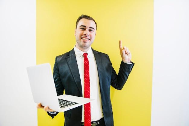 指を持ち上げているノートパソコンを持つ流行の男