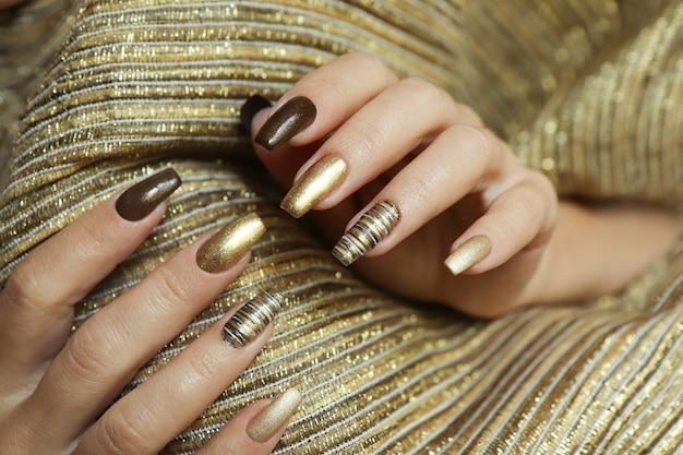 매니큐어의 무광택 황금색과 긴 손톱 모양에 갈색의 트렌디 한 매니큐어.
