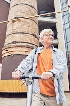 Модный зрелый мужчина на скутере