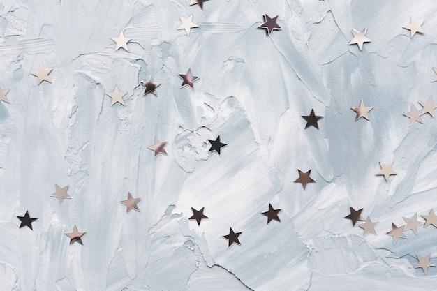 Модные металлические звезды конфетти фольги на белом и синем светлом фоне. зимний абстрактный фон. день рождения, новый год, празднование рождества, праздники и концепция мечты. выборочный фокус