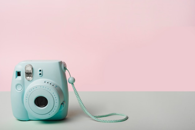 Trendy mini instant camera against pink background