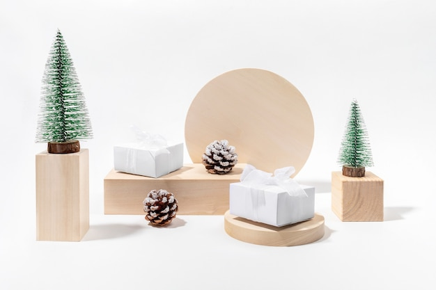 Trendy minimal xmas holiday composition with christmas decorations on wooden podiums in neutral color.