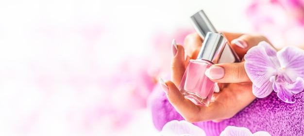 트렌디한 네일 매니큐어. 손톱 광택제를 들고 여자 손입니다. 난초에서 핑크 장식입니다.