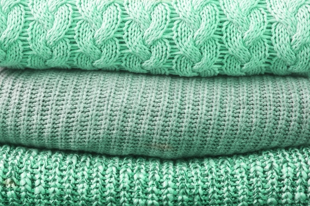 Trendy neo mint tissue clothes texture. close up of sweaters stack.