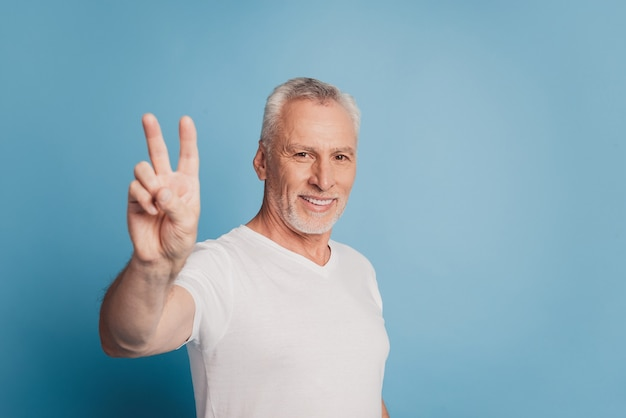 Trendy old man showing v-sign isolated blue background