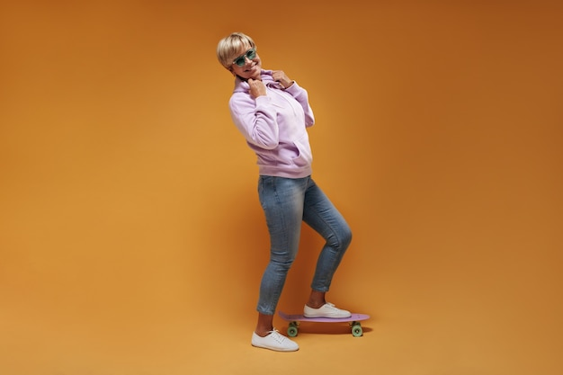 Trendy old woman with blonde hairstyle in pink cool sweatshirt, jeans and white sneakers smiling and posing with skateboard.