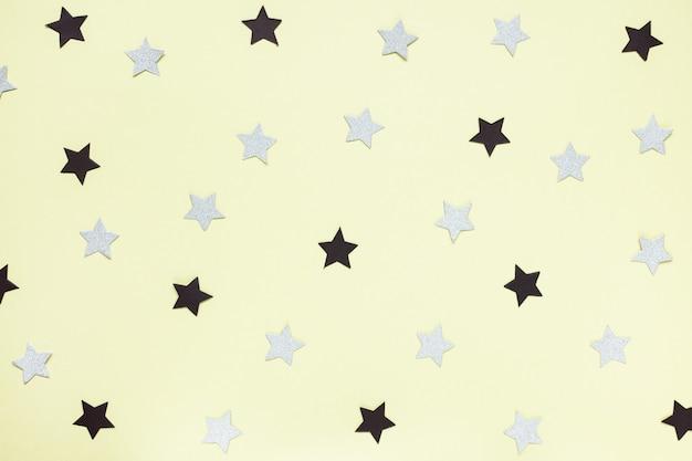 黄色の背景にトレンディな紙の黒と灰色の紙吹雪の星。