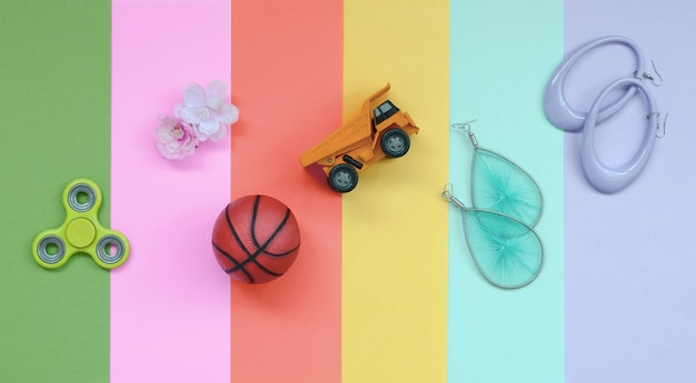 Trendy pastel composition with earrings, sunglasses, beverage can, basketball ball, toy truck, flower and spinner