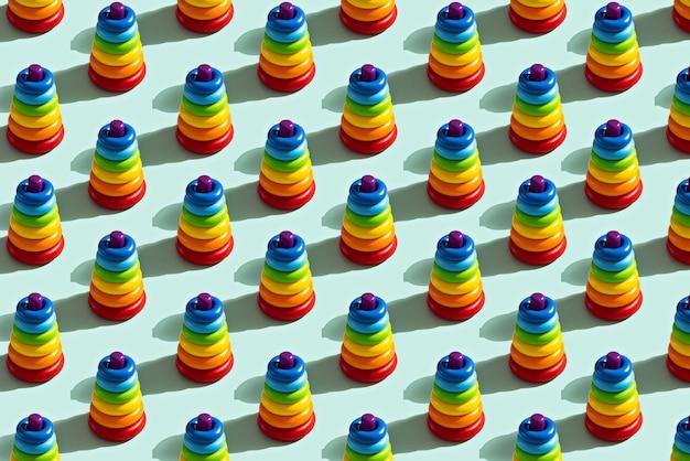 Модный узор красочной игрушечной пирамиды на синем фоне, концепция детства