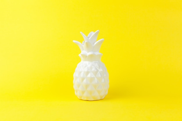 黄色の紙の背景にインテリアの白い光沢のあるセラミックパイナップルのトレンディな作品
