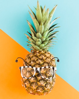 Trendy pineapple in sunglasses on multicolored background