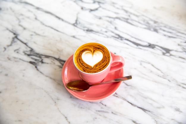 대리석 테이블 배경에 핫 카푸치노의 트렌디한 핑크 컵. 사랑의 상징을 위한 하트 모양의 라떼 아트. 아침 루틴에 한 컵.