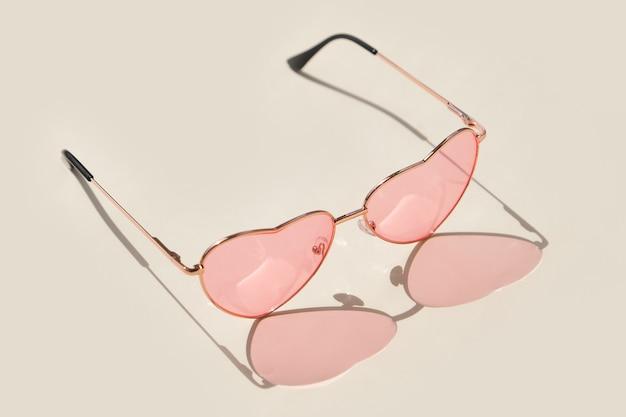 パステルカラーの表面に日光の影と反射神経を備えたハートの形をしたトレンディなピンクのサングラス