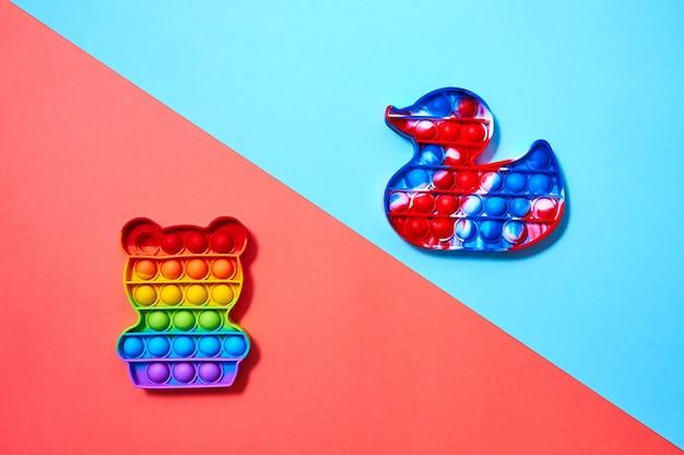 カラフルな赤と青の背景にクマとアヒルの形でトレンディなポップイットおもちゃ。上面図フラットレイ