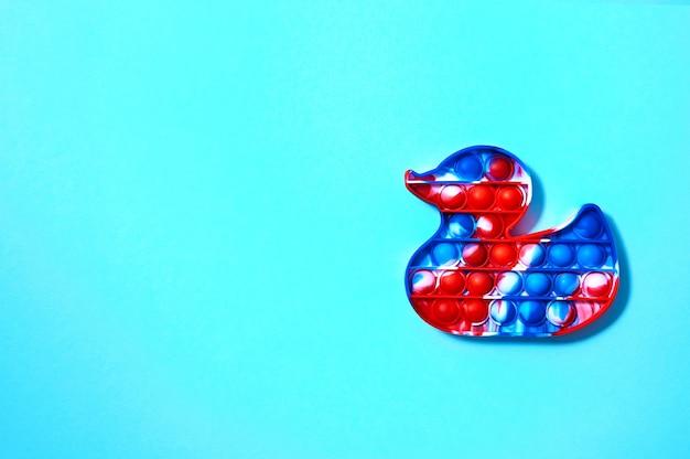 Модные игрушки pop it в виде утки на синем фоне, вид сверху, плоская планировка, копировальное пространство