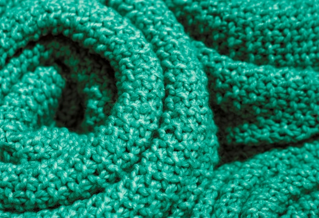 Trendy quetzal green color woolen knitted fabric close-up, texture, background