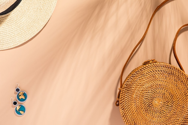 Trendy rattan bag on natural tone background. female fashion travel concept. flat lay, top view, trendy fashion style. eco design.
