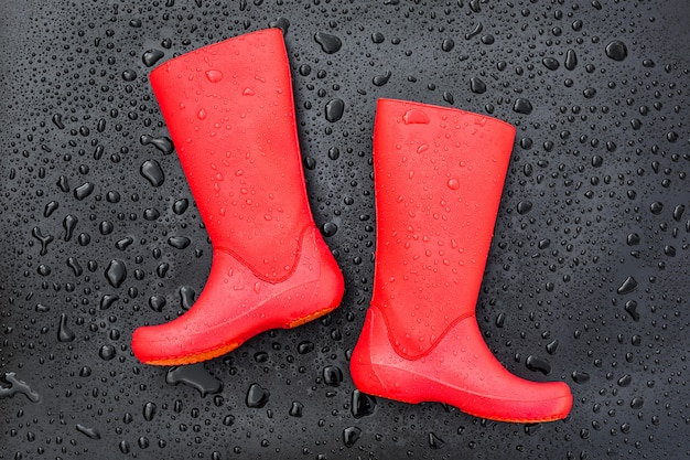 Trendy red rubber boots on black wet surface covered with raindrops. top view.