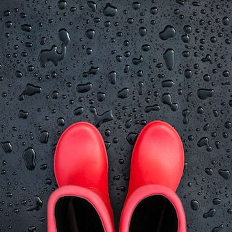 Trendy red rubber boots on black wet surface covered with raindrops.