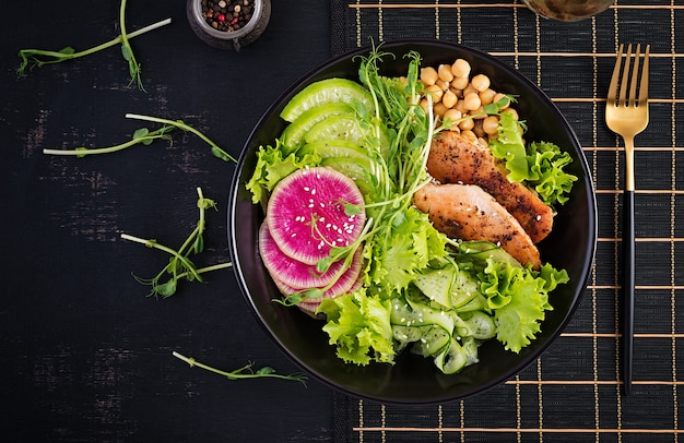 Trendy salad. buddha bowl dish with chicken fillet, chickpea, cucumber, radish,  fresh lettuce salad, pea sprouts  and chia seeds. healthy food. top view, overhead, copy space