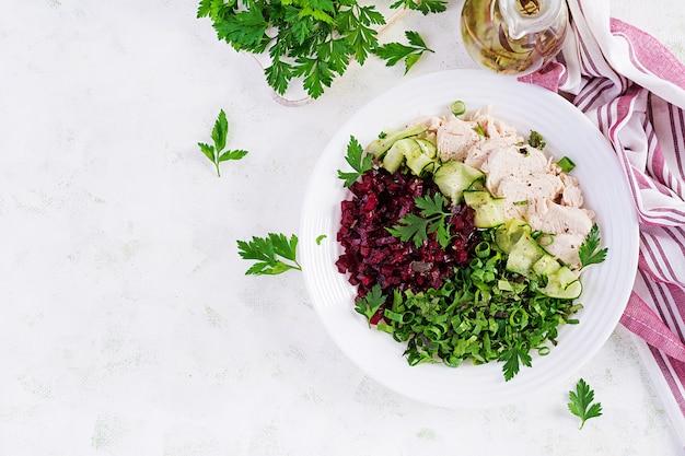 トレンディなサラダ。チキンボイルフィレのサラダビートルートとキュウリ。健康食品、ケトン食療法、ダイエットランチのコンセプト。ケト/パレオダイエットメニュー。上面図、オーバーヘッド