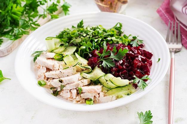 トレンディなサラダ。チキンボイルフィレのサラダビートルートとキュウリ。健康食品、ケトン食療法、ダイエットランチのコンセプト。ケト/パレオダイエットメニュー。