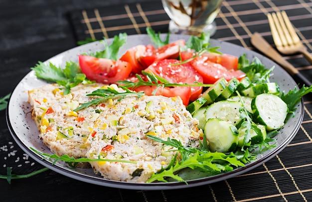 Модный салат. куриный рулет с салатом из свежих помидоров и огурцов. здоровое питание, кетогенная диета, концепция диетического обеда. кето, меню палеодиеты.