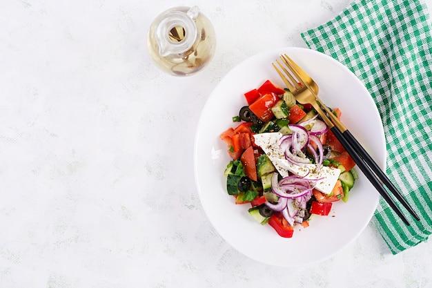 トレンディなサラダ。新鮮な野菜、フェタチーズ、ブラックオリーブのギリシャ風サラダ。健康的なバランスの取れた食事。上面図、オーバーヘッド、フラットレイ