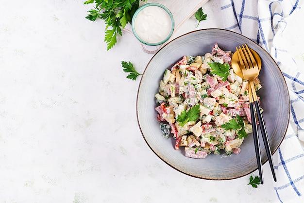 トレンディなサラダ。ハム、パプリカ、きゅうり、チーズのサラダ。健康食品、ケトン食療法、ダイエットランチのコンセプト。ケト/パレオダイエットメニュー。上面図、オーバーヘッド