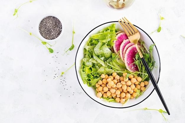 트렌디 한 샐러드. 병아리 콩, 수박 무, 오이, 완두콩 콩나물을 곁들인 채식주의 부처 그릇. 건강한 균형 잡힌 식사. 평면도, 오버 헤드, 플랫 레이